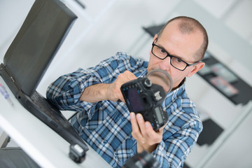 worker investigating a digital camera