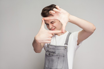 Portrait of young brunette man in casual style with white t-shirt and denim overalls standing and looking at camera and making camera frame with hands. indoor studio shot, isolated on gray background.