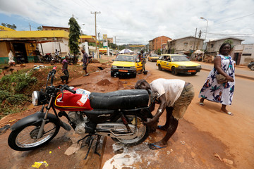 Woman wearing a dress with a printed photograph of Cameroon President Paul Biya, who runs for re-election on Oct. 7, walks past a man washing his motorcycle in Yaounde,