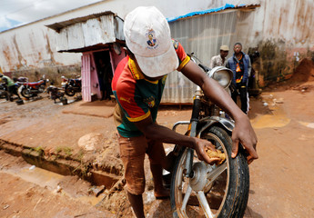 A man washes his motorcycle as he wears a cap with a picture of Cameroon President Paul Biya, who runs for re-election scheduled for October 7, in Yaounde