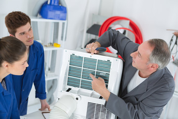 young students learning to adjust air conditioning system