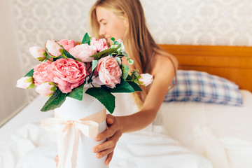 beautiful girl with peony flowers sitting on the bed. She just woke up and got a bouquet of flowers