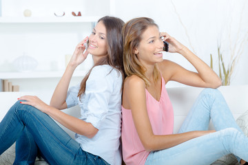 sisters siting back to back and using phone at home