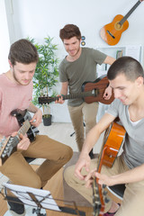 teenagers playing guitar at home