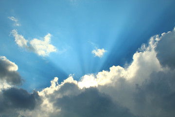 Beautiful blue sky and cumulus clouds. Sun rays. Background. Landscape.