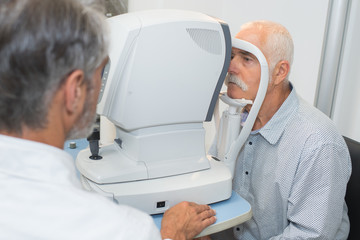 Patient resting chin on ophthalmologist's equipment