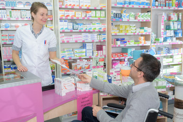 helpful pharmacist serving a disable man in a pharmacy