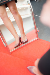 View of woman's legs and shoes in shop mirror