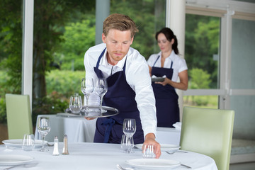 waiter setting glassware on table