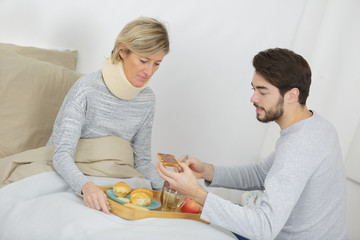 son assisting ill mother lying in bed