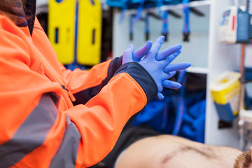Emergency doctor putting on gloves in ambulance
