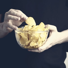 Young man in black having a bowl of potatoes chips in his hands. Selective focus.