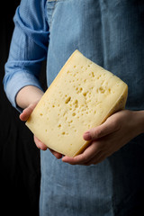 Woman holding slice of cheese wearing blue apron on dark background