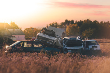Cars lined up on each other on junkyard in the sunset