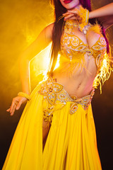 Close up of traditional oriental belly dancer girl dancing on yellow neon smoke background. Unrecognizable woman in exotic costume with feathers sexually moves her hips.