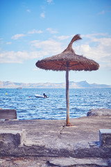 Vintage toned picture of a straw beach umbrella, summer holidays concept, selective focus.