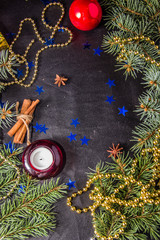 black leather background with Christmas tree branches tinsel rowan red candle cone and blue stars and a place for an inscription
