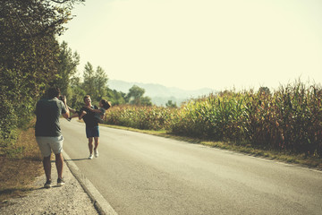 videographer recording while couple jogging along a country road