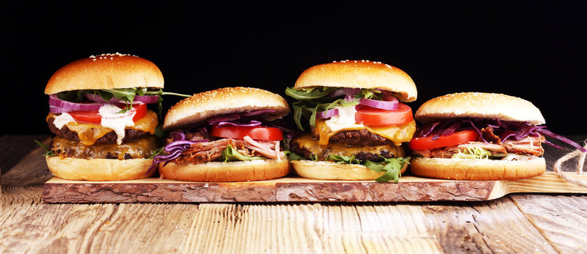 Tasty fresh meat burgers with salad and cheese. Homemade angus burger and Pulled pork sandwiches.