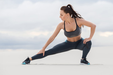Fitness woman doing lunges exercises for leg muscle workout training, outdoor. Sporty girl doing stretching exercise
