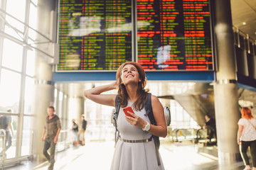 Theme travel and tranosport. Beautiful young caucasian woman in dress and backpack standing inside train station or terminal looking at a schedule holding a red phone, uses communication technology
