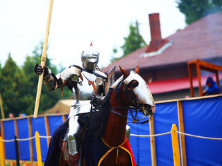 Knight in armor with a big pike in his hand is riding a thoroughbred horse. Historic reconstruction concept Wall mural