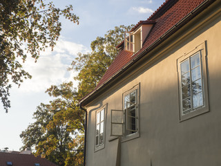 old prague baroque house at Kampa with open window in golden hour light, trees and sky background