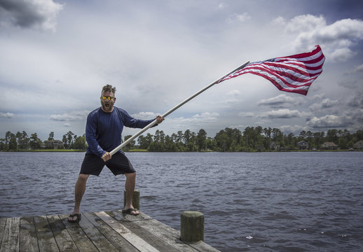 Cheerful man waving American flag while standing on pier over lake against cloudy sky at Banff National Park