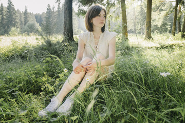 Full length of thoughtful young woman looking away while sitting on grassy field in forest