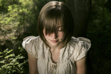 High angle view of young woman with eyes closed and bangs in forest