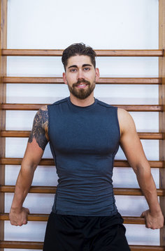 Portrait of confident muscular athlete standing against wall bars in gym