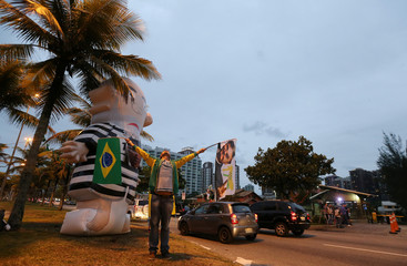 A supporter of Brazilian presidential candidate Jair Bolsonaro is seen next to an inflatable doll, also known as Pixuleco, depicting former Brazilian president Luiz Inacio Lula da Silva, in front of Bolsonaro's condominium in Rio de Janeiro