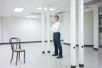 Businessman standing in empty bright office and looking  smiling at camera.