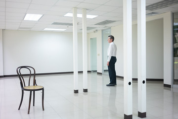Businessman standing in empty bright office and look out thinking