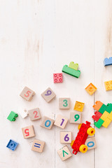 Top view on wooden cubes with numbers 2019 and multi-color toy bricks on old white wooden background. Toys in the table. Early learning and development.