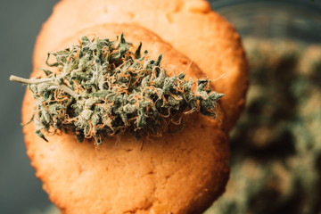 Sweets with cannabis. Cannabis buds on a black background. Baking with the addition of CBD. Sweets with weed. Cookies with marijuana.