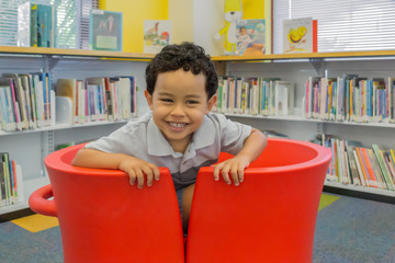 A happy little boy sits in two red U-shape chairs pushed together.