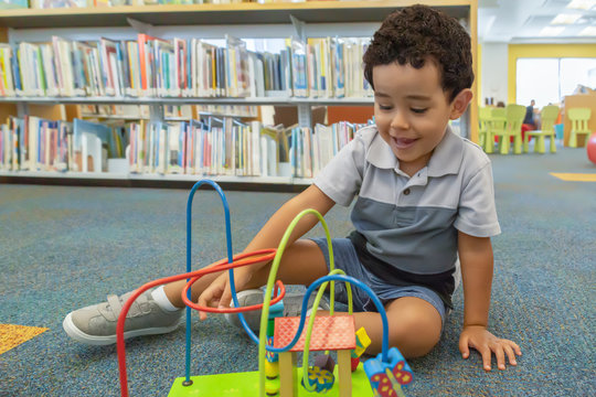 A happy little boy sits on the carpet playing at the library.