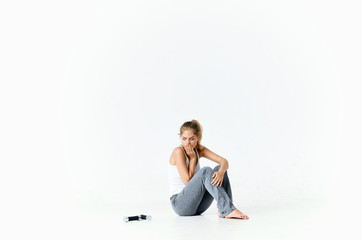young woman sitting on the floor over isolated background