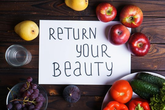 Dieting, healthy lifestyle, eating quality improvement and whole foods. Conscious nutrition and motivation concept. Inscription Return your beauty with organic fruits and vegetables on table