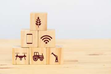 Wall Mural - smart farm or agriculture futuristic technology concept, wooden cube icon connect, icon including wireless wifi, ai or artificial intelligence, cloud, phone, sensor, truck, robot, drone, factory