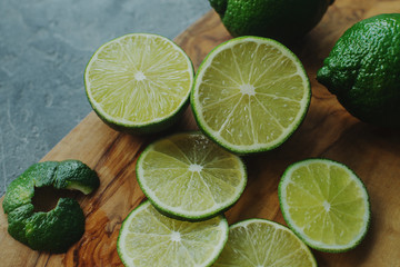 Fresh juicy organic lime in slices on wooden board and dark stone background. Ripe fruit, healthy lifestyle, selective focus