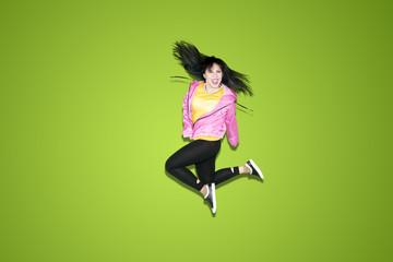 Happy female dancer jumping on studio