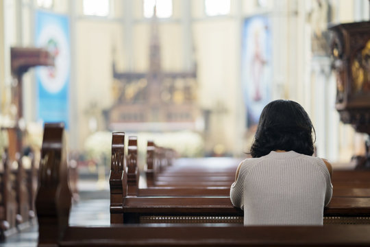 Religious woman praying in the church