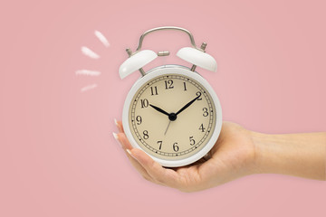 Hands holding alarm clock on pink bacground