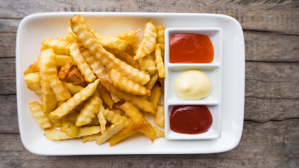 French fries in a white dish with ketchup and chili sauce on wooden floor.