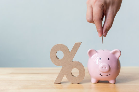 Hand putting money coin in piggy bank with percentage sign symbol