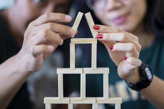 Young couple building a house of blocks