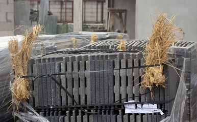 Large pack of building materials on a construction site in south east Asia packed with hay on the corners for cushioning to protect against breakages.