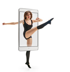 Photo of young beautiful modern female dancer jumping, concept virtual reality of the smartphone. going out of the device